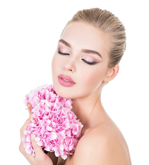 Young beautiful woman with flowers near face.