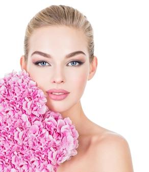 Молодая красивая женщина с цветами возле лица.