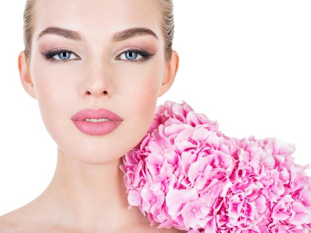 Giovane bella donna con fiori vicino al viso.