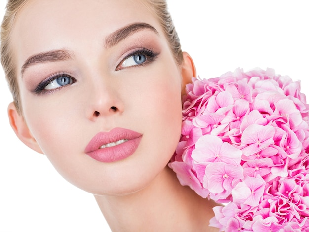 얼굴 가까이 꽃과 젊은 아름 다운 여자. 무료 사진