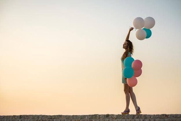 Молодая красивая женщина с летающими разноцветными воздушными шарами против неба. концепция счастья и мечты