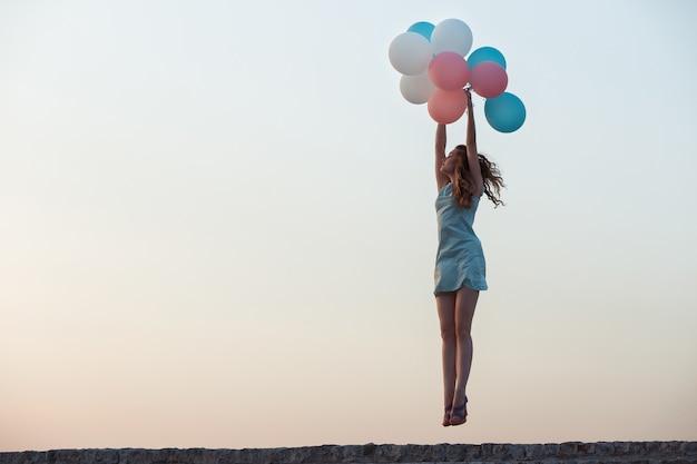 Молодая красивая женщина с летающими разноцветными воздушными шарами прыгает против неба. концепция счастья и мечты