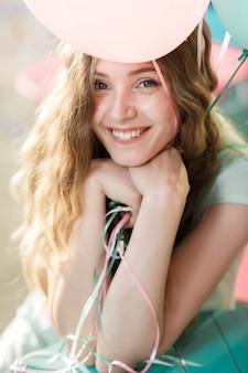 カメラを見て色とりどりの風船を飛んでいる若い美しい女性。幸せと夢のコンセプト。