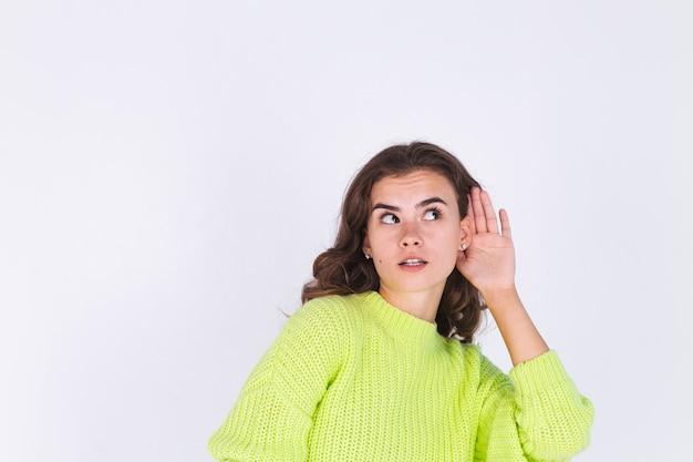 白い壁のゴシップトークのセーターでそばかすの軽い化粧をしている若い美しい女性は秘密を聞く