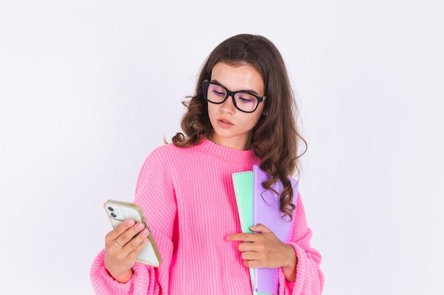 흰 벽에 스웨터를 입은 주근깨 빛 화장을 한 젊은 미녀, 휴대폰으로 화면을 사려깊은 표정으로