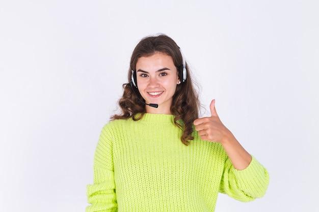 헤드폰 헬프라인 직원 콜센터 매니저 행복한 미소를 지으며 흰 벽에 스웨터를 입은 주근깨 빛 화장을 한 젊은 미녀