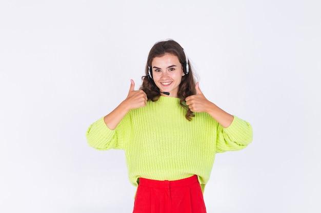 そばかすのある若い美しい女性は、ヘッドフォンヘルプラインワーカーコールセンターマネージャーの幸せな笑顔で白い壁にセーターで軽い化粧をします