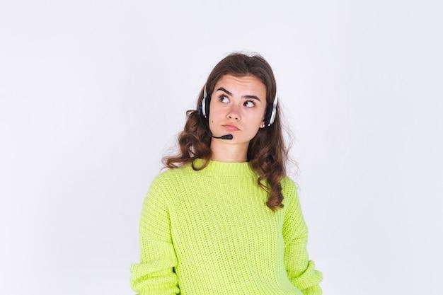 헤드폰 헬프라인 직원 콜센터 매니저가 있는 흰색 벽에 스웨터를 입고 주근깨 빛 화장을 한 젊은 미녀