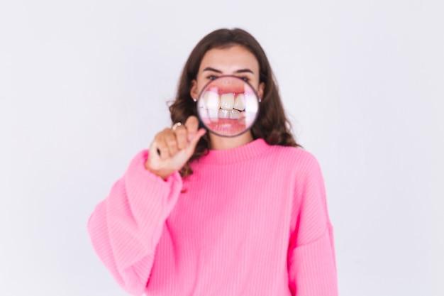 Молодая красивая женщина с веснушками и легким макияжем в свитере на белой стене с лупой показывает идеальную улыбку с белыми зубами