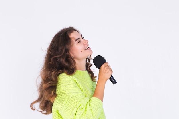 흰 벽에 스웨터를 입고 주근깨 빛 화장을 한 젊은 미녀, 마이크가 행복한 노래