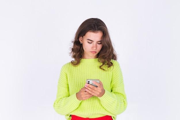 흰 벽에 스웨터를 입고 주근깨가 있는 밝은 화장을 한 젊은 미녀, 휴대폰으로 심각하게 슬픈 화가