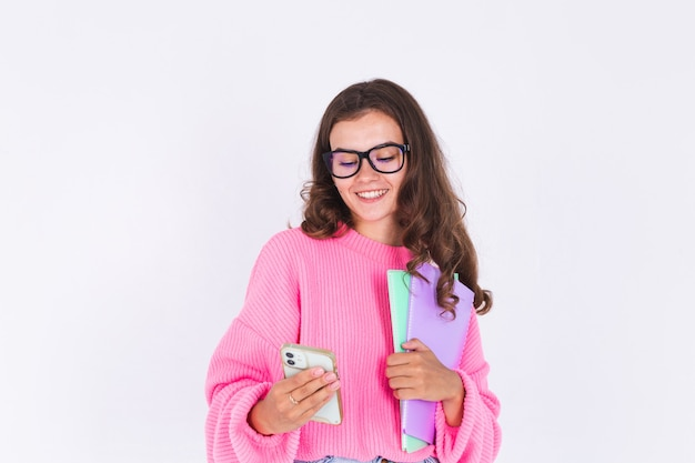 Young beautiful woman with freckles light makeup in sweater on white wall student with mobile phone thoughtful look at screen and smile