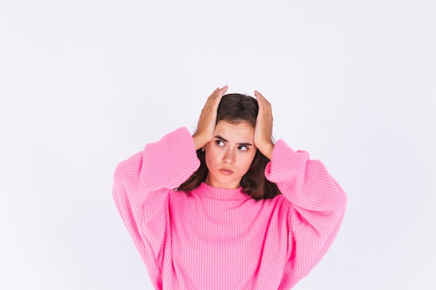Giovane bella donna con lentiggini trucco leggero in maglione sul muro bianco che soffre di mal di testa