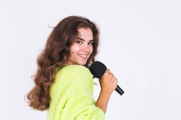 Young beautiful woman with freckles light makeup in sweater on white wall with microphone happy singing  moving