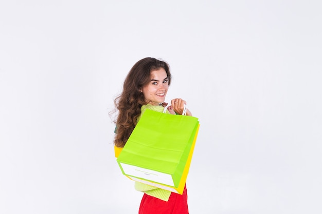 Young beautiful woman with freckles light makeup in sweater on white wall with shopping bags cheerful happy excited