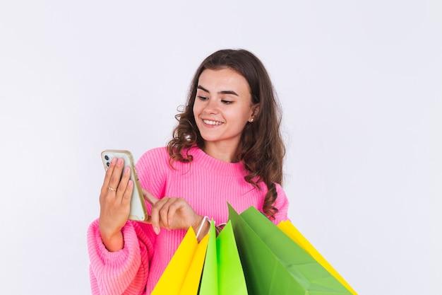 Giovane bella donna con lentiggini trucco leggero in maglione sul muro bianco con borse della spesa e telefono cellulare sorridente allegro positivo