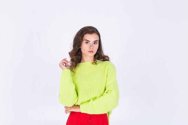 Young beautiful woman with freckles light makeup on white wall posing