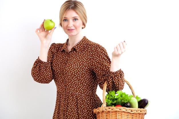 Молодая красивая женщина с ведром свежих овощей на белом фоне