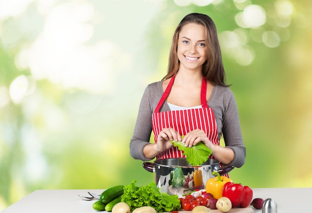 Young beautiful woman with fresh vegetables cooking
