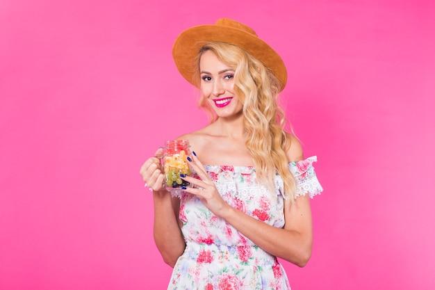 コピースペースとピンクの背景にフルーツ瓶を持つ若い美しい女性