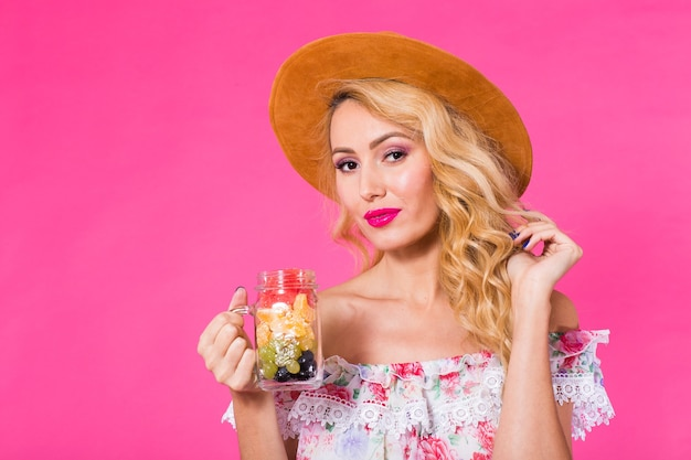 ピンクの背景にフルーツ瓶と若い美しい女性