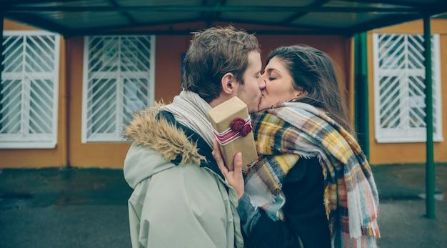 추운 가을날 야외에서 깜짝 선물을 손에 들고 남자친구에게 키스를 하는 아름다운 젊은 여성. 사랑과 부부 관계 개념입니다.
