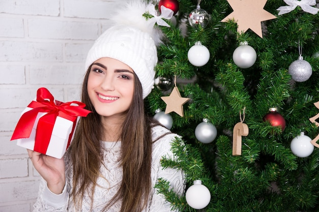 Young beautiful woman with gift box near decorated christmas tree