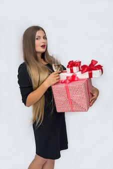 Молодая красивая женщина с подарочными коробками и бокалом в студии
