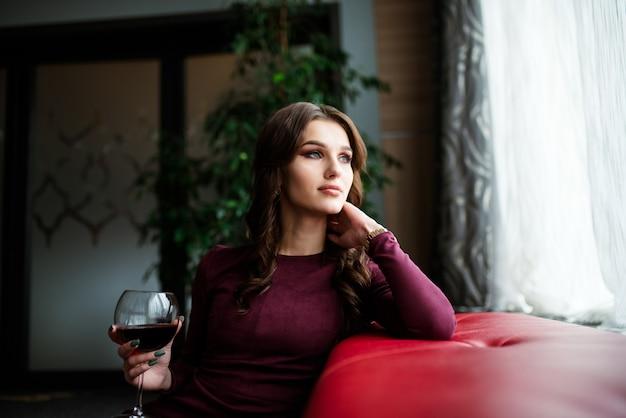 カメラ目線の赤ワインのグラスを持つ若い美しい女性