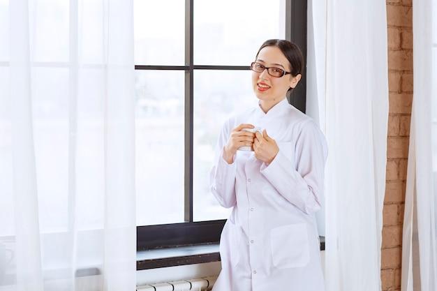 창 근처에 서 있는 실험실 코트에 안경을 쓴 젊은 아름 다운 여자.