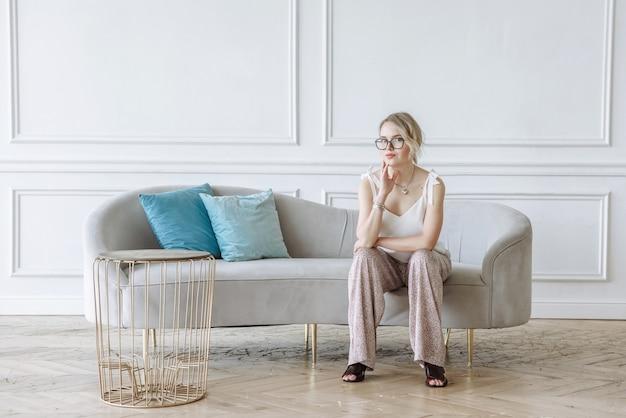 ソファに座って、自宅の屋内でカメラを見ている眼鏡をかけた若い美しい女性
