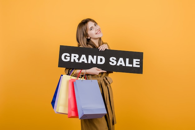 Young beautiful woman with grand sale  sign and colorful shopping bags isolated over yellow