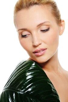 그녀의 어깨를 덮고 녹색 잎을 가진 젊은 아름 다운 여자