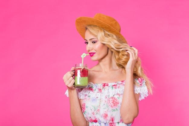 コピースペースとピンクの壁に緑のスムージーと若い美しい女性