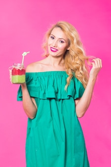 ピンクの壁に緑のスムージーを持つ若い美しい女性。