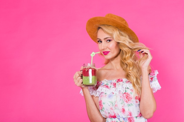 Young beautiful woman with green smoothie on pink background with copyspace