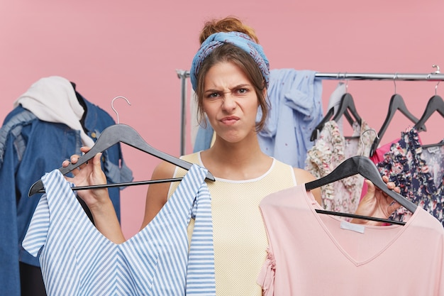 Young beautiful woman with grumpy expression, frowning her face with dissatisfaction while holding two dresses, having no suitable size for her. discontent woman having problems during shopping