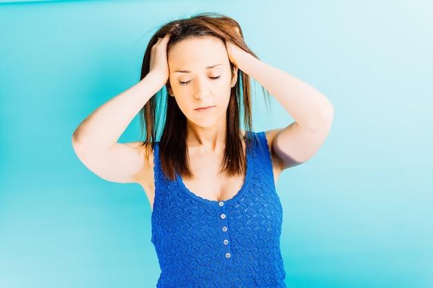 파란색 배경으로 머리에 손을 대고 고통스러운 스트레스를 받는 젊은 아름다운 여성