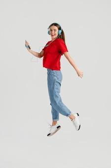 ジャンプするヘッドフォンを持つ若い美しい女性 Premium写真