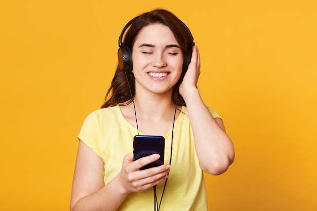 黄色に分離されたお気に入りの音楽を聴くヘッドフォンで若くてきれいな女性
