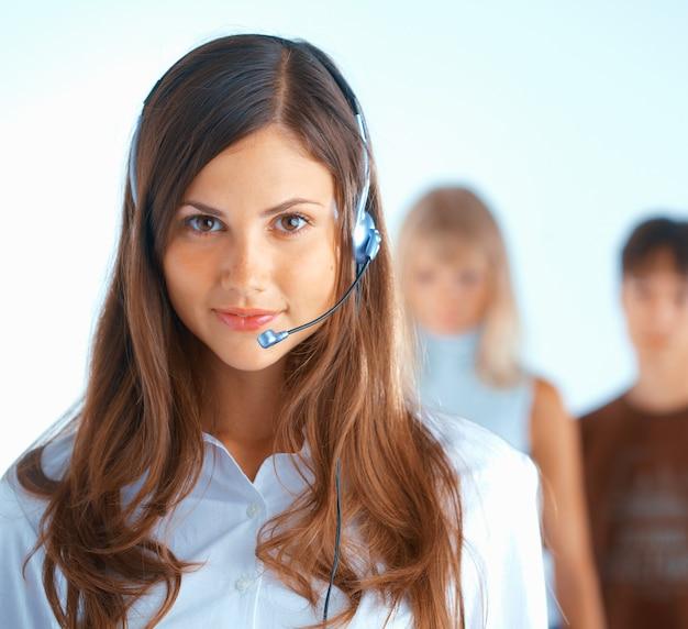 バックグラウンドで何人かの人々とヘッドセットを持つ若い美しい女性