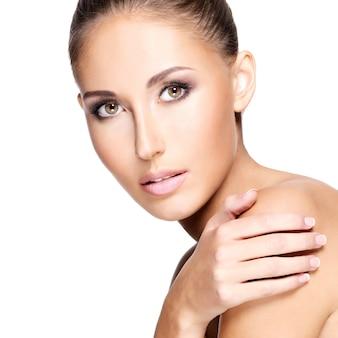 흰색 절연 그녀의 어깨를 만지고 건강 한 피부를 가진 젊은 아름 다운 여자.