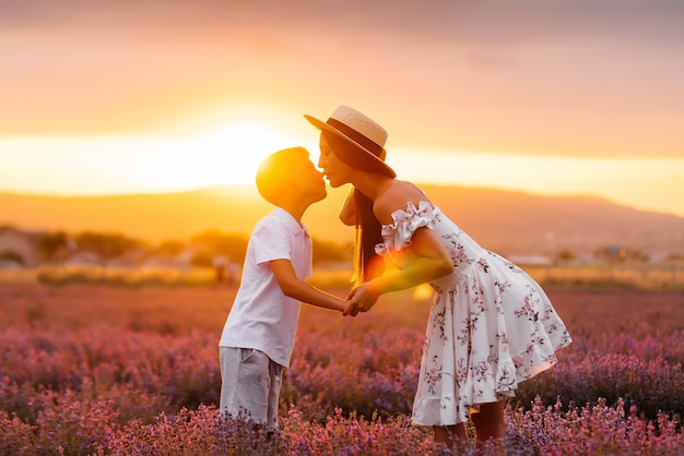 A young beautiful woman with her young son is walking through a beautiful field of lavender and enjoying the fragrance of flowers. rest and beautiful nature. unity with nature and harmony.