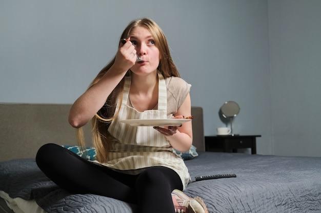 Молодая красивая женщина с интересом смотрит телевизор и ест