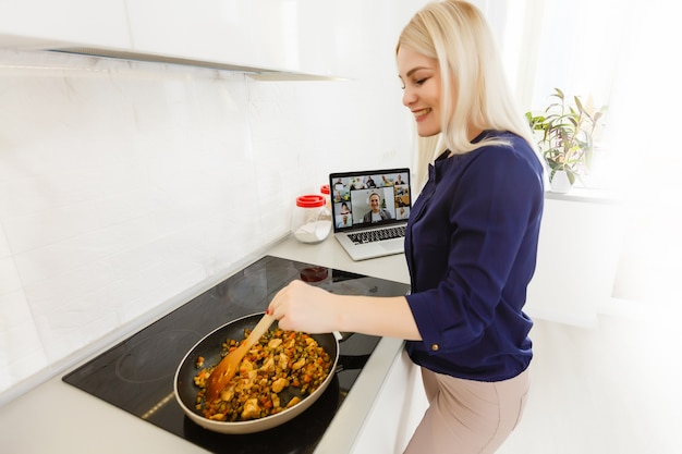Young beautiful woman with laptop in the kitchen, looking for recipe