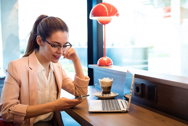 Young beautiful woman with laptop , smartphone and coffee in a restaurant