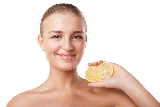 白の上のレモンと若い美しい女性