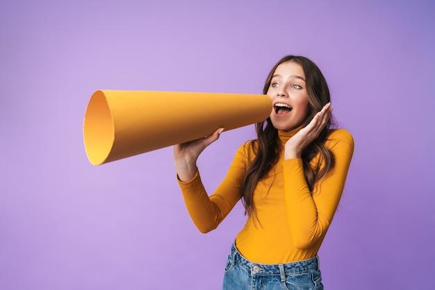 Молодая красивая женщина с длинными каштановыми волосами улыбается и говорит на изолированной бумаге мегафон