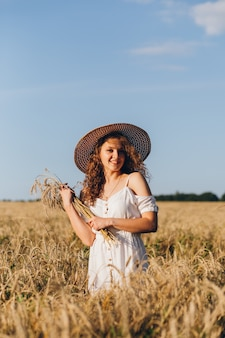 Young beautiful woman with long curly hair poses in a wheat field in the summer at sunset