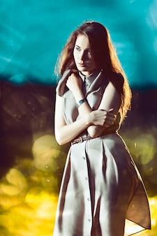 반짝이 벽에 긴 머리를 가진 젊은 아름 다운 여자